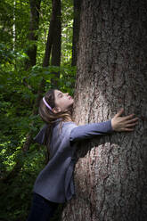 Cute elementary girl hugging tree trunk in forest - LVF08906