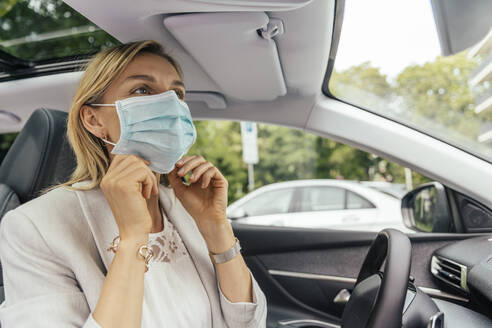 Portrait of woman in car putting on protective mask - MFF05584