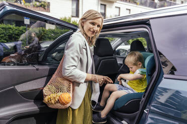 Portrait of smiling woman waiting in front of car while her little son fastening seat bell of child's seat - MFF05590