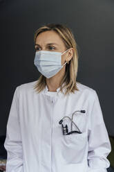 Portrait of doctor wearing protective mask against grey background - MFF05623