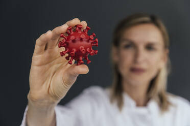 Hand of female scientist holding 3D model of SARS-CoV-2 virus, close-up - MFF05629
