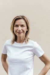 Portrait of smiling blond woman wearing white t-shirt in front of light wall - MFF05635