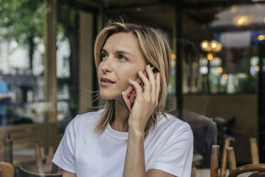 Portrait of woman on the phone in front of a coffee shop - MFF05644