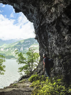 Mature man with backpack standing by rock formation while looking at Lake Como from cave entrance - MCVF00397