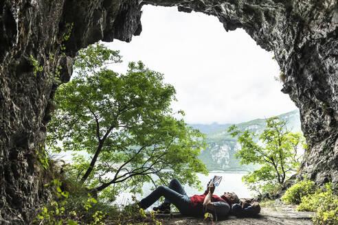 Mature man reading book while lying at cave entrance by Lake Como - MCVF00400