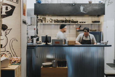 Male chefs preparing food behind counter at illuminated restaurant kitchen - PSIF00393
