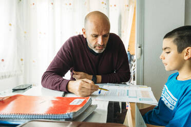 Confident father teaching son while sitting at desk during homeschooling - JCMF00762