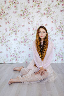 Portrait of confident young woman with long brown hair sitting against floral wallpaper - TCEF00702