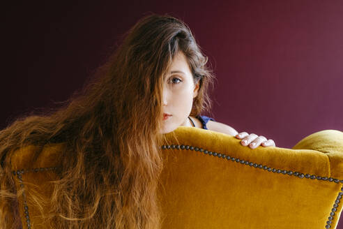 Close-up portrait of young woman with long brown hair leaning on golden chair against colored background - TCEF00708