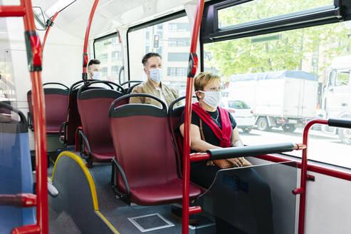 Passengers wearing protective masks in public bus, Spain - DGOF01040