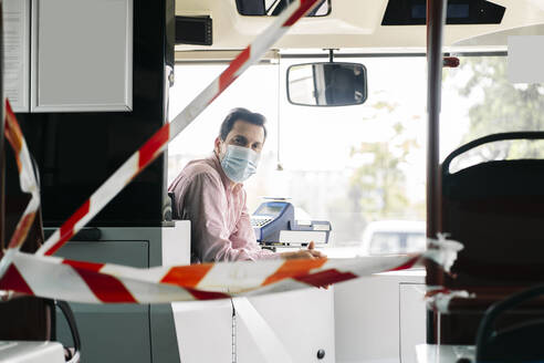 Portrait of mature bus driver wearing protective mask behind caution tape in public bus, Spain - DGOF01049