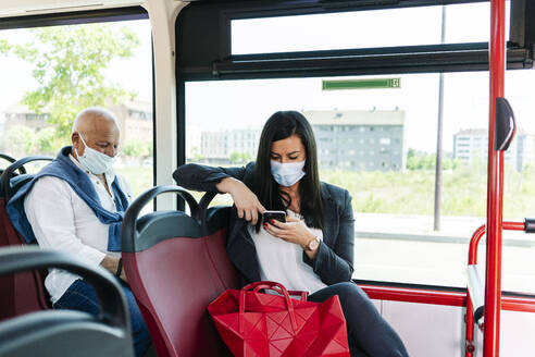 Businesswoman wearing protective mask sitting in public bus using cell phone, Spain - DGOF01067