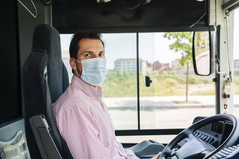Portrait of mature bus driver wearing protective mask, Spain - DGOF01073