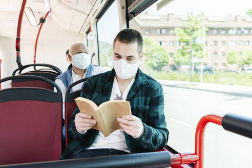 Portrait of young man wearing protective mask and gloves in public bus reading a book, Spain - DGOF01076