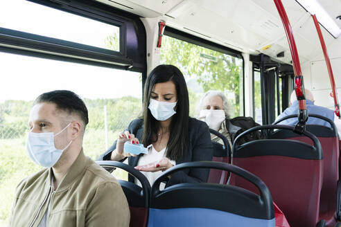Woman wearing protective mask in public bus disinfecting her hands, Spain - DGOF01079