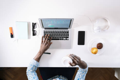 Man holding coffee while using laptop at desk in home office - JCMF00765