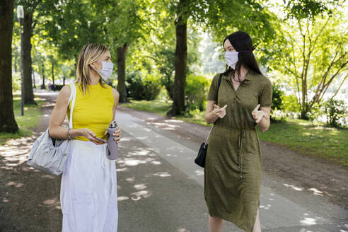 Two women meeting in nature while wearing face masks - MFF05690
