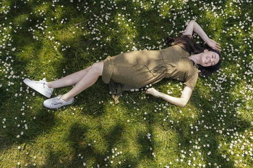 Woman enjoying her free time while lying on grass with daisies - MFF05705