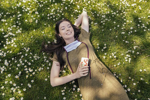 Woman with let down face mask enjoying her free time while lying on grass with daisies - MFF05708