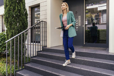 Real estate agent with digital tablet and face mask in hand walking down stairs of house - MFF05714