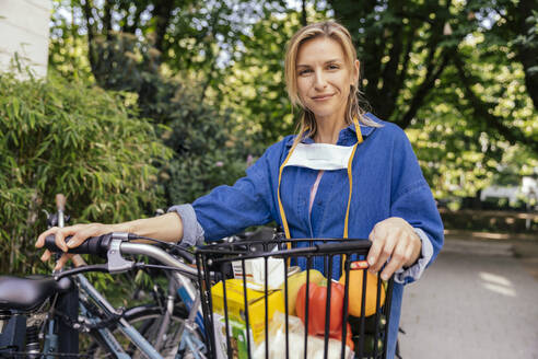 Portrait of confident woman with let down face mask and bicycle and groceries - MFF05732