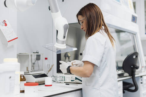 Confident female scientist working at laboratory - OCAF00495