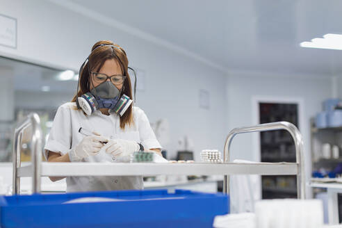 Confident mature female technician holding marker while looking at pills in lab - OCAF00507