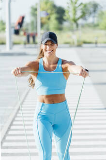Portrait of smiling young woman exercising with resistance band on sunny day - OCMF01291