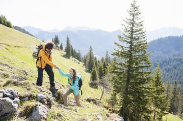 Man helphing his woman climbing rock, Wallberg, Bavaria, Germany - DIGF11656