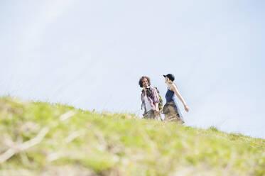 Hiking couple on meadow in summer, Wallberg, Bavaria, Germany - DIGF11671