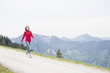 Smiling woman with hiking poles, Wallberg, Bavaria, Germany - DIGF11680