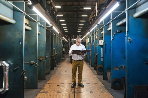 Senior businessman with folder in a factory hall - DIGF11832