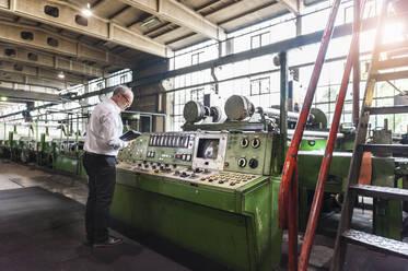 Senior businessman examining a machine in a factory hall - DIGF11859
