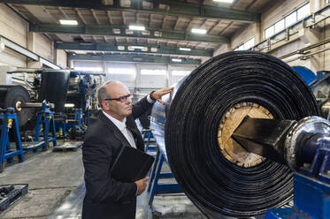 Senior businessman examining product in a rubber processing factory - DIGF11865