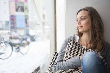 Portrait of daydreaming woman in a coffee shop looking through window in winter - DIGF12027
