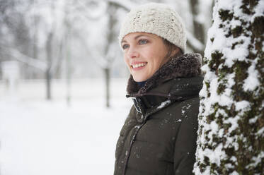 Portrait of smiling woman leaning at tree trunk in winter - DIGF12033