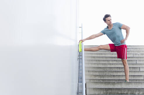 Handsome mid adult man stretching leg on wall while standing over steps - DIGF12048