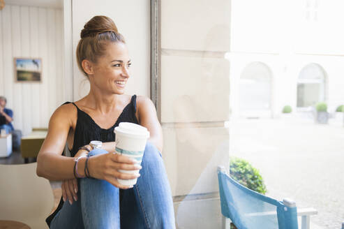 Portrait of laughing woman with bun sitting in a coffee shop looking out of window - DIGF12057