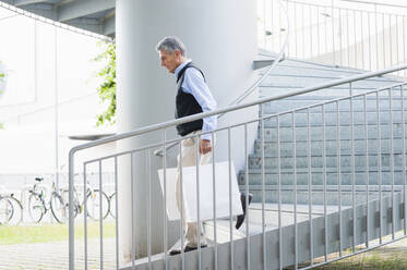 Senior man with shopping bags walking downstairs - DIGF12081