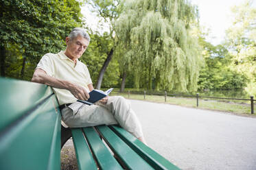 Portrait of senior man sitting on park bench reading a book - DIGF12087