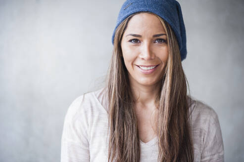 Happy woman with long brown hair wearing knit hat against gray wall - DIGF12111
