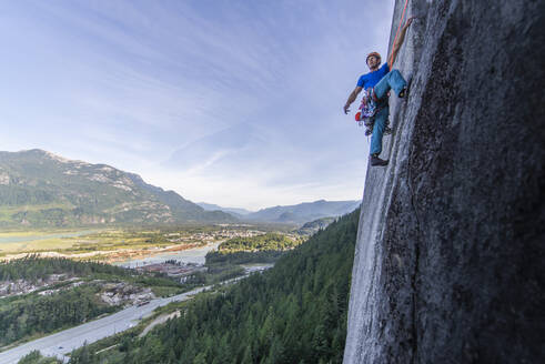 Man lead climbing granite Squamish with background view of valley - CAVF82329