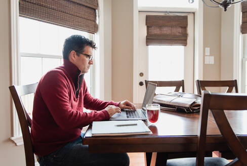 Man in glasses working from home using a computer at a dining table. - CAVF82344