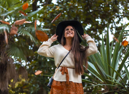 A young brunette in a fall photo session with falling tree leaves - CAVF82806