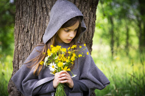 Girl holding bunch of yellow wildflowers - LVF08912