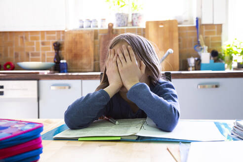 Girl doing homework in kitchen at home, hands on face - LVF08918