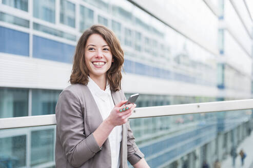 Happy businesswoman holding smart phone while standing outside glass building - DIGF12185