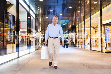 Portrait of happy senior man with shopping bag in a shopping center - DIGF12260