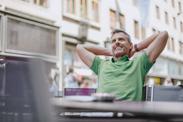 Smiling thoughtful mature man with hands behind head sitting on chair at sidewalk cafe - DIGF12265