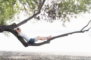 Woman relaxing on tree trunk at Ammersee, Germany - DIGF12409